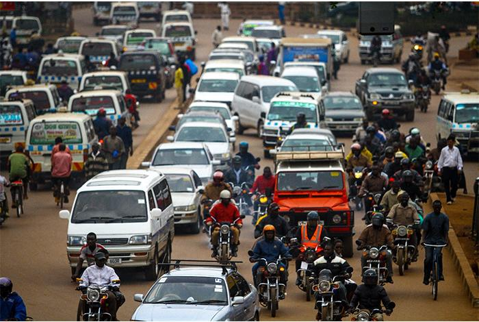 photo, Tugende, street scene in Uganda with cars, people on motorbikes, and bicyclists, DFC, OPIC, US International Development Finance Corporation