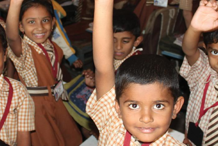photo, Indian children in classroom smile with raised hands and waving