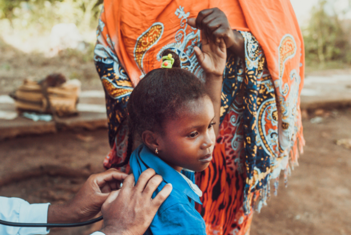 African doctor with stethoscope, checking child patient