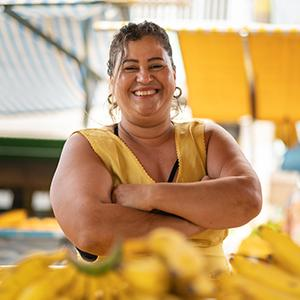 photo of woman wearing yellow standing with arms crossed and smiling