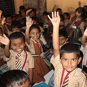 photo, children in classroom in India wave and raise their hands