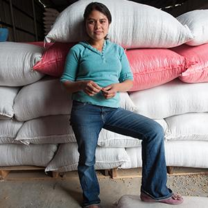 photo, woman standing in front of grain bags