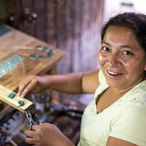 photo, woman creating jewelry and smiling